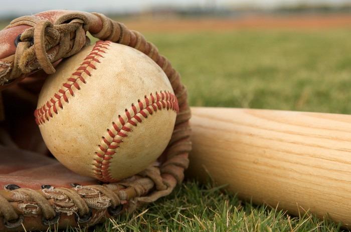 Baseball mitt, ball, and bat on grass.